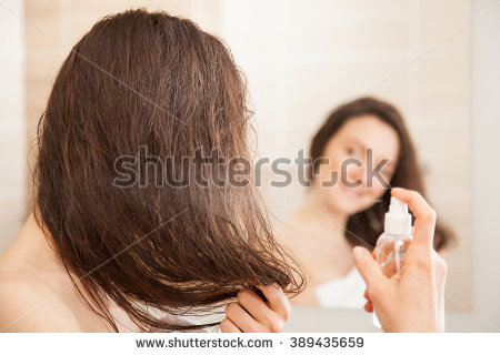stock-photo-smiling-young-woman-applying-hair-spray-in-front-of-a-mirror-haircare-concept-389435659